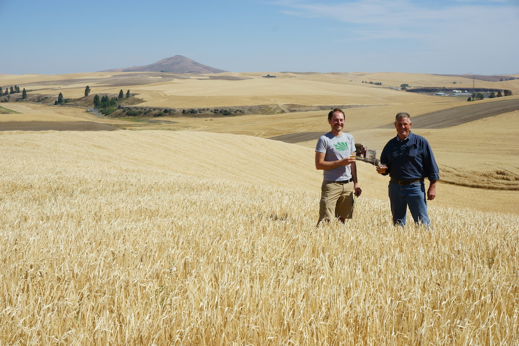 Maltster Joel Williamson and farmer Bill Myers of Joseph's Grainery salute the field with a beer