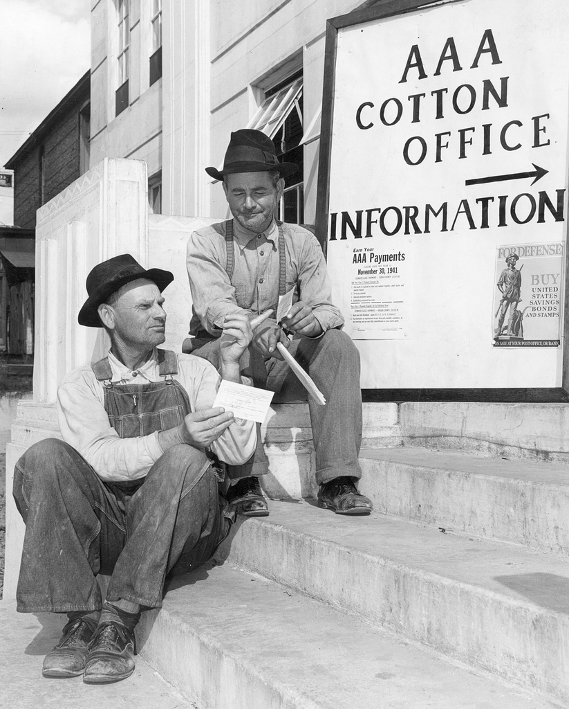 farmers talk in front of a Agricultural Adjustment Act sign