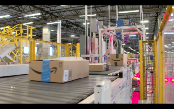 A conveyor belt in an Amazon fulfillment center warehouse moves boxes