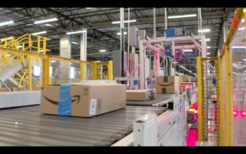 A conveyor belt in an Amazon fulfillment center warehouse moves boxes