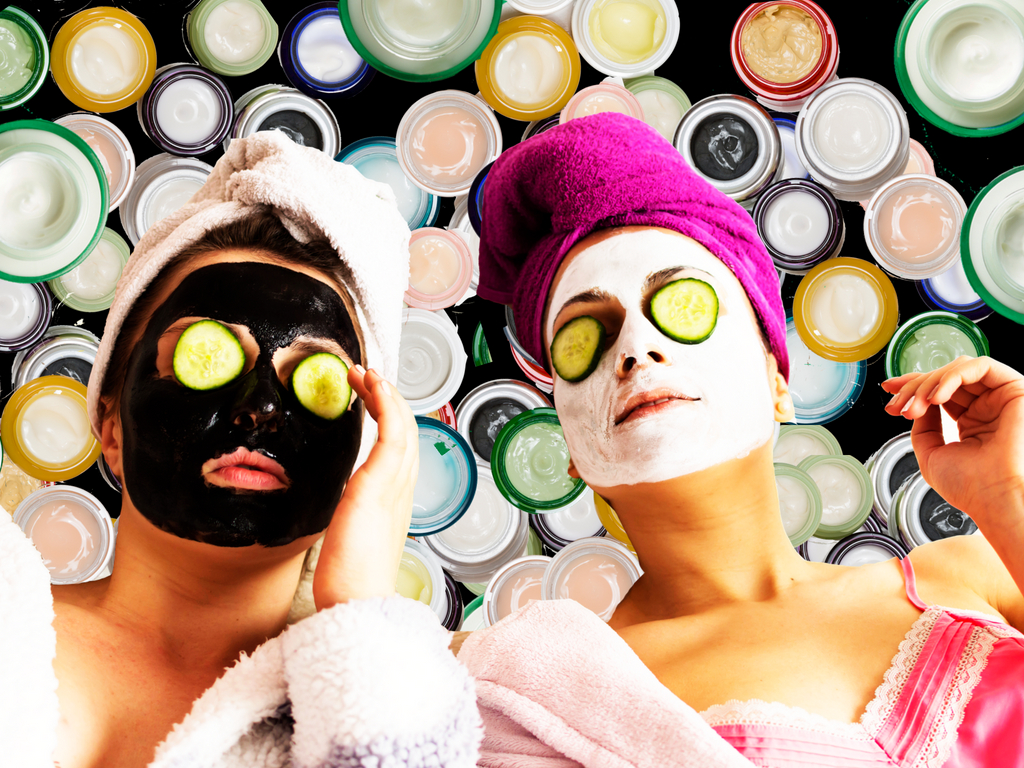 two women with cucumbers on their eyes and face masks, in front of jars of face cream