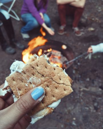 hand holding bitten s'more at a campfire