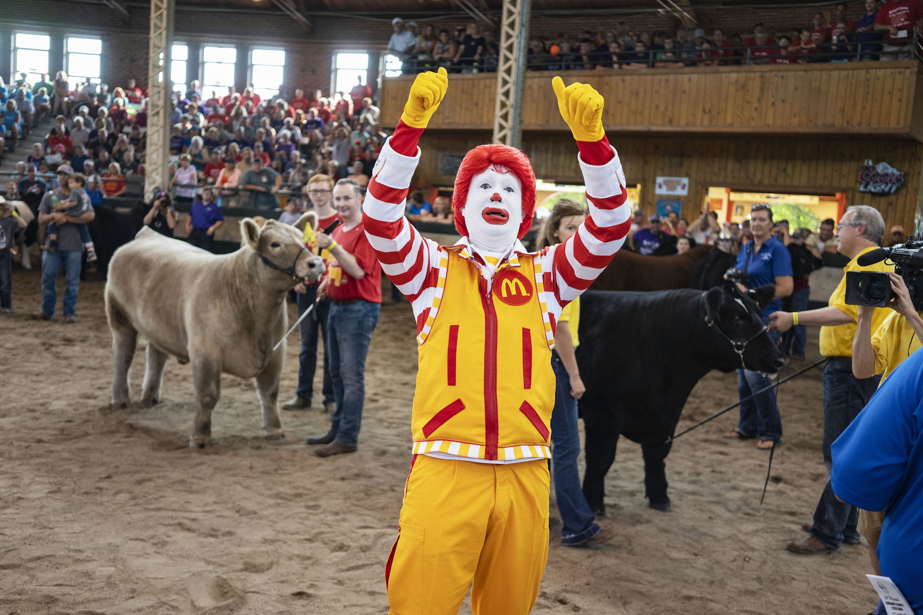 A man dressed as Ronald McDonald gives a thumps up to to audience members during The Governor's Charity Steer Show at The Iowa State Fair in Des Moines, Iowa on Saturday, August 11, 2018.