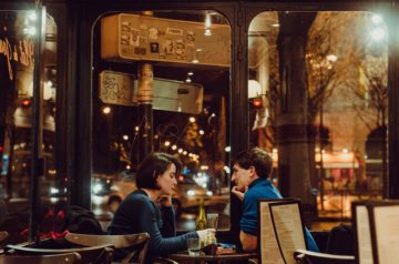 Couple on a date in front of a cafe.