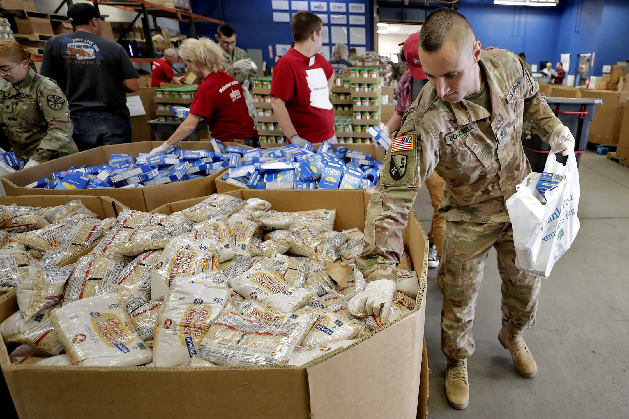 Members of the Arizona National Guard pack and sort food items at a food bank Thursday, March 26, 2020, in Mesa, Ariz.