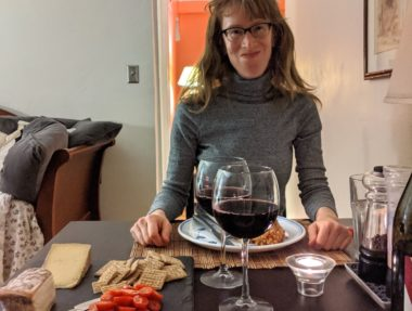 Kyle McCarthy at her home restaurant with barley risotto wine and cheese May 2020