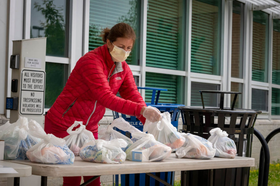 A woman wearing a mask sets out separated school lunch bags onto a plastic table for distribution during Covid-19. June 2020