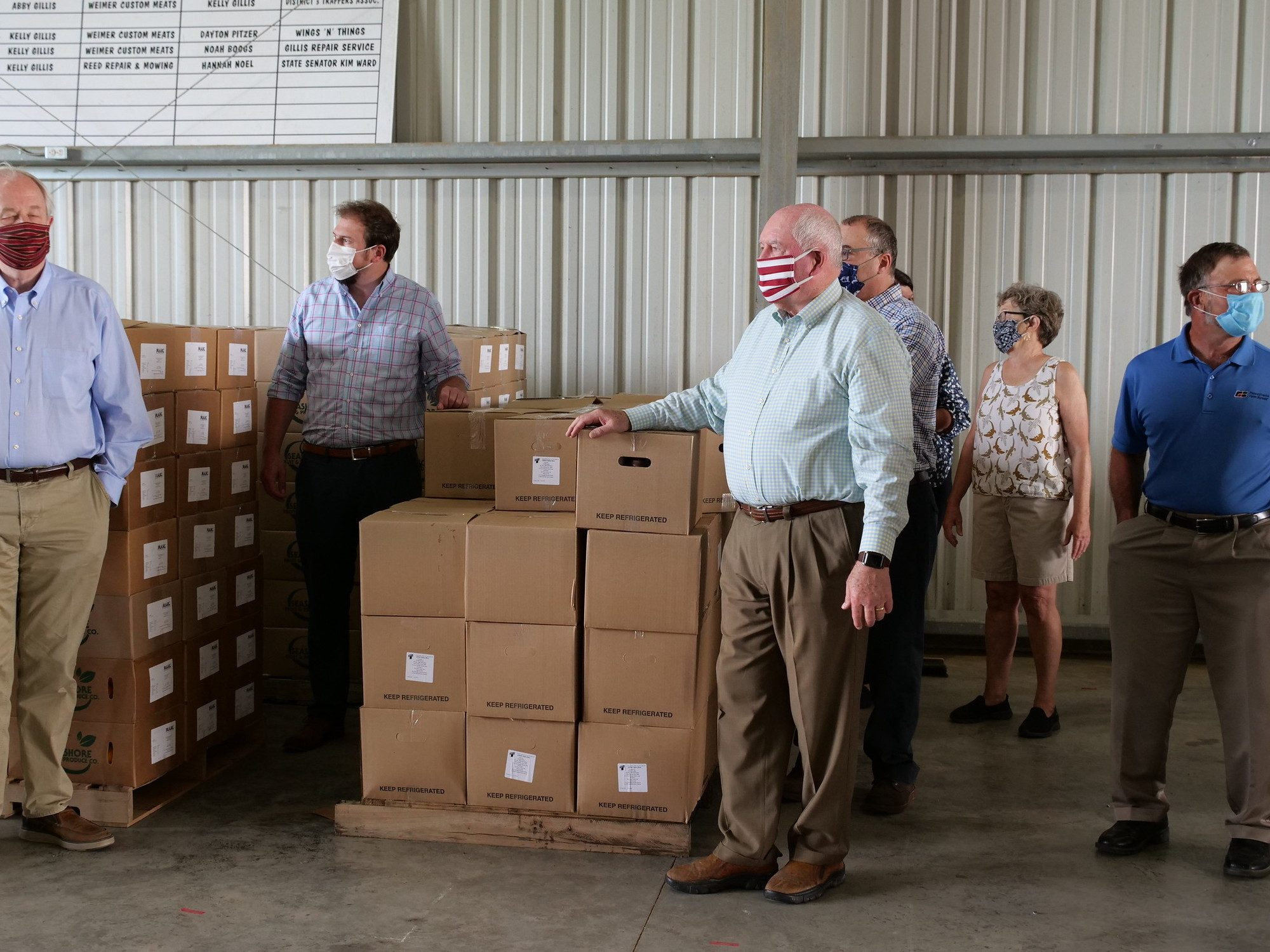 Sonny Perdue, standing with his left had rested on a stack of food boxes, participating in Farmers for Families event in Greensburg, PA.