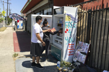 Volunteers Bryant Rodriguez and his daughter Vanessa stock a refrigerator with free food in Los Angeles. July 20, 2020.