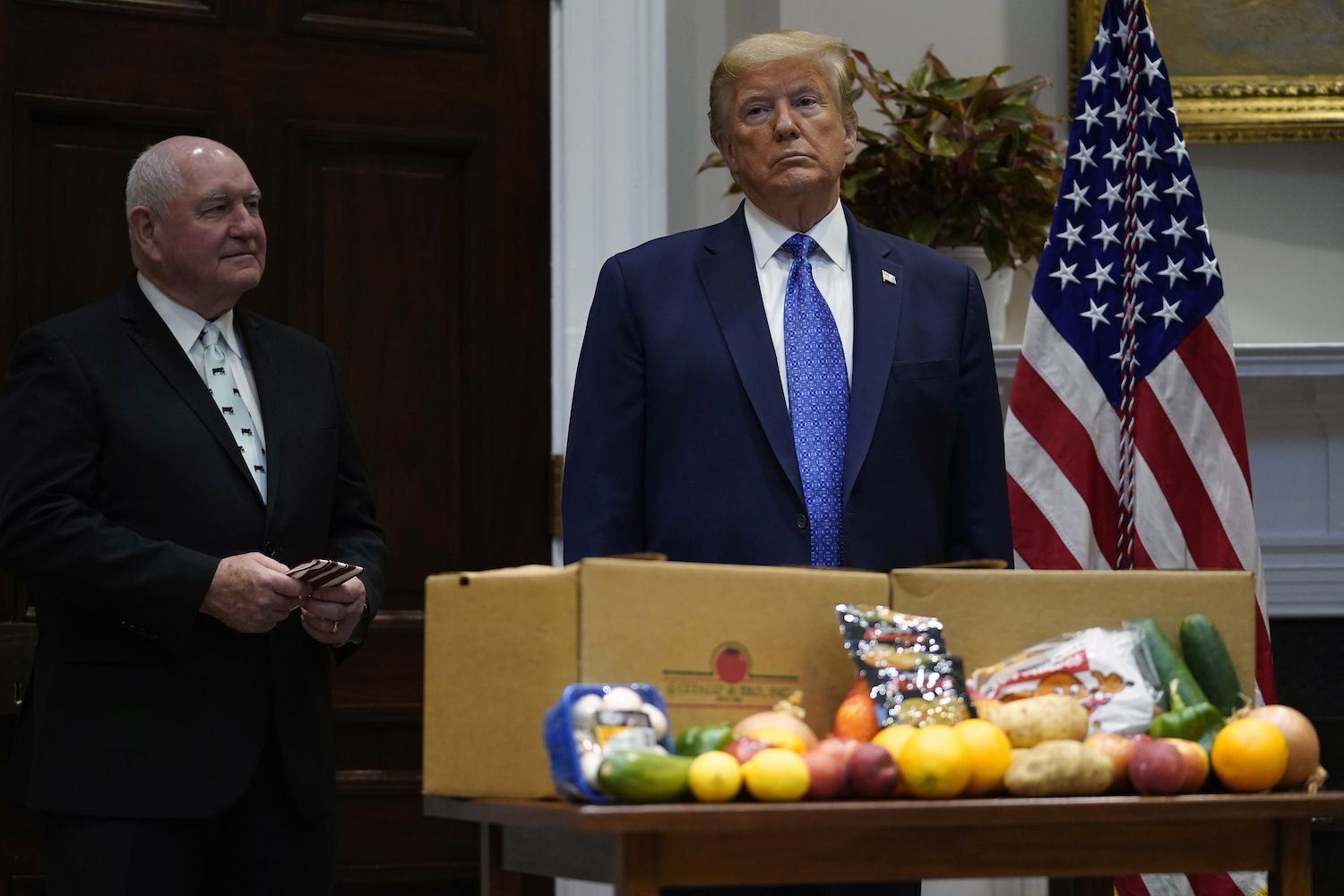 Agriculture Secretary Sonny Perdue and President Donald Trump attend an event on the food supply chain during the coronavirus pandemic, in the Roosevelt Room of the White House, Tuesday, May 19, 2020, in Washington.