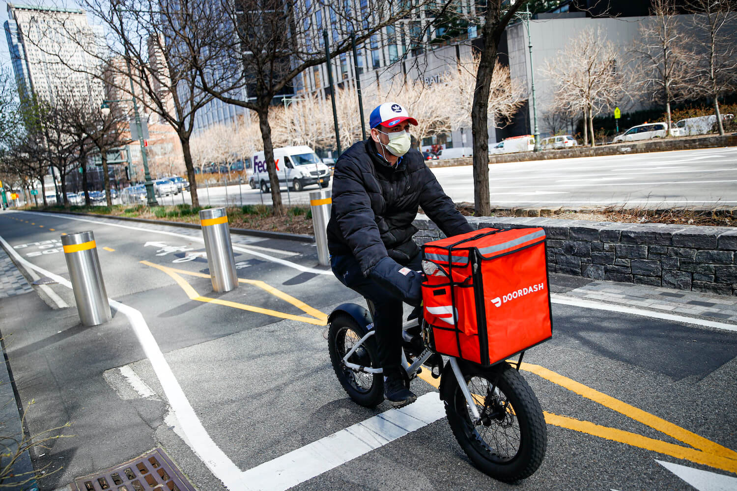 A Doordash delivery gig worker rides his bike down a street. November 2020