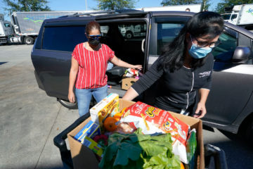 Johnna Nieves, left, opens her van as Idalia Nunez, right, of the Second Harvest Food Bank loads the vehicle with a weeks supply of food in Orlando, Fla., on Tuesday, Nov. 17, 2020. While food banks have become critical during the pandemic, they're just one path for combating hunger. For every meal from a food bank, a federal program called Supplemental Nutrition Assistance Program, or food stamps _ provides nine. December 2020