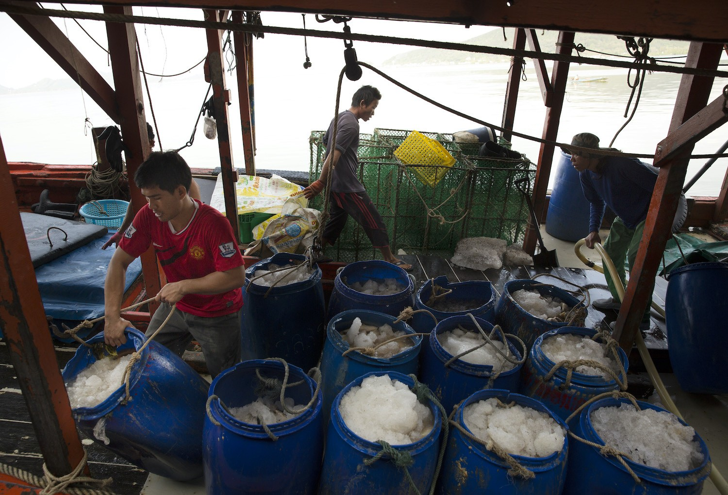 Barrels of fish packed on ice sit on fishing boat about to be unloaded at the port in Songkhla on February 2, 2016. Around 100 people have been arrested by authorities in a recent crackdown on abuses involving Thailand's multi-billion dollar seafood industry. The deep-rooted problem caused the huge global brand, Nestle in 2015 to admit that it had discovered clear evidence of slavery at sea in parts of the Thai supply chain. Thailand is the world's third largest exporter of seafood. February 2021