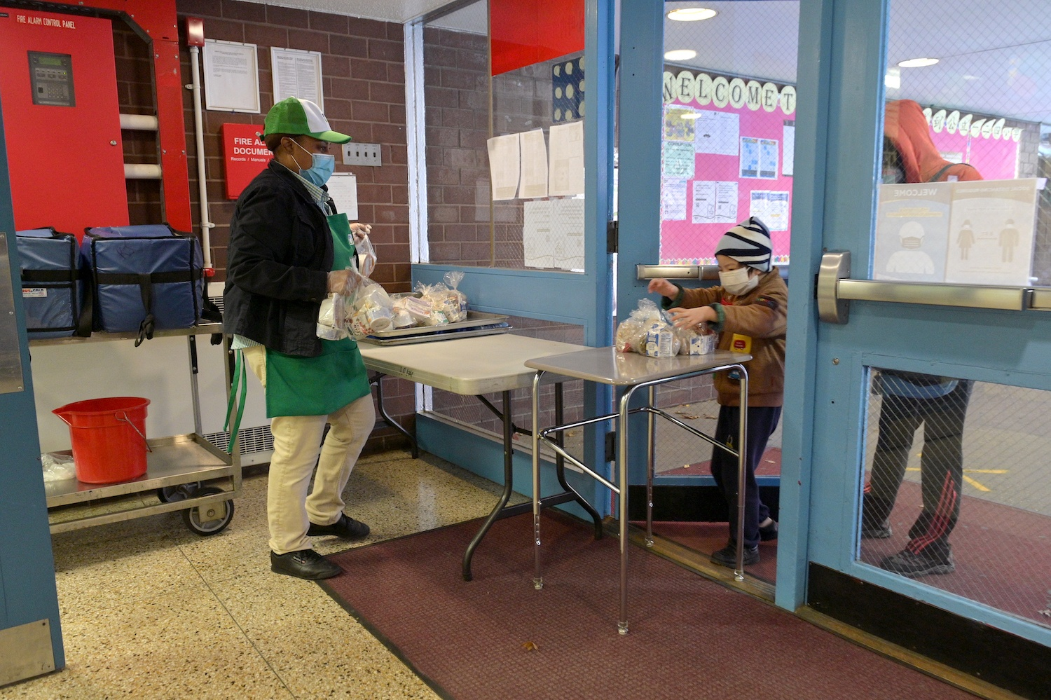 A student chaperoned by an adult picks up a meal to go on November 19, 2020 at Yung Wing School P.S. 124 in New York City.
