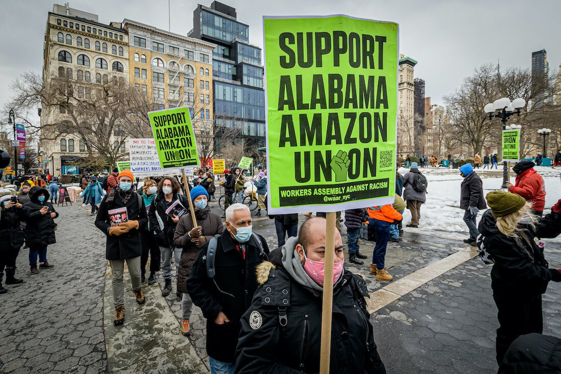 2021/02/20: Participants seen holding signs and marching on a picket line at the protest. Members of the Workers Assembly Against Racism gathered across from Jeff Bezos-owned Whole Foods Market in Union Square South for a nation-wide solidarity event with the unionizing Amazon workers in Bessemer, Alabama. March 2021