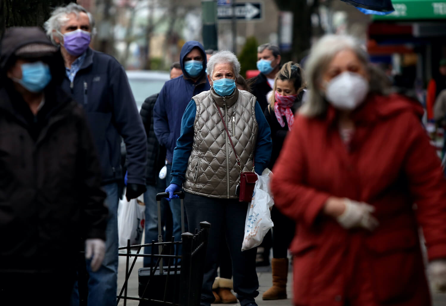 A line of masked people wait to pick up food from Biancardis on Arthur Ave. in the Bronx, NY, on April 10, 2020. March 2021