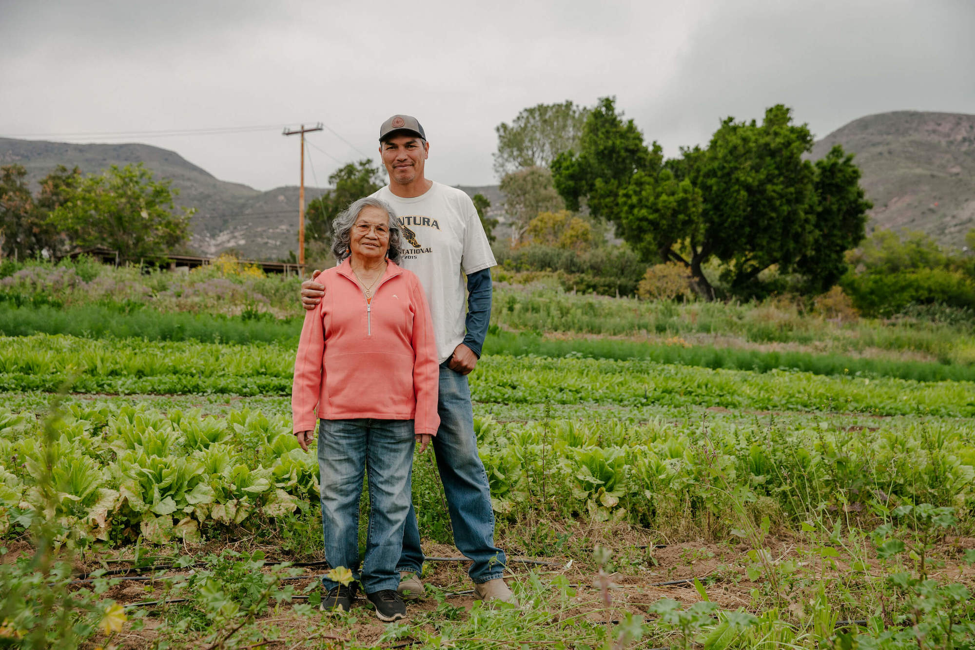 Romeo holding his mom Fidela while standing in a field on their family farm. May 2021