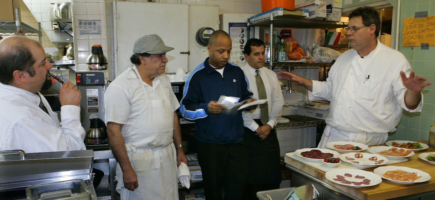 Chef Don Dickman, right, explaining the new menu to employees inside the kitchen. Story about Matteo's, a 40–year old restaurant in Westwood on the first night of the changing of the menu for the first time. November 14, 2006