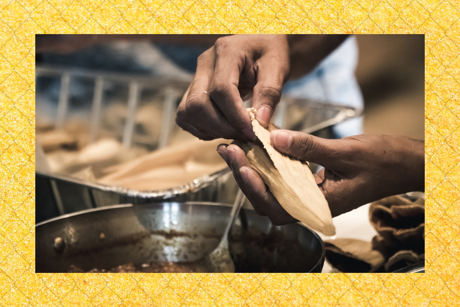 Brown hands prepare tamales with a fence and cornmeal border. June 2021