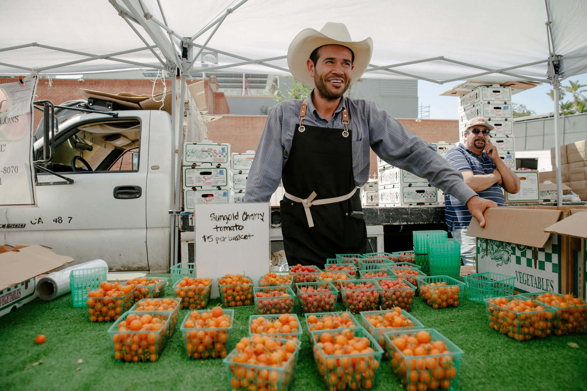 Victor Gomez, ranch foreman of Munak Ranch, stands with cherry tomato display. August 2021