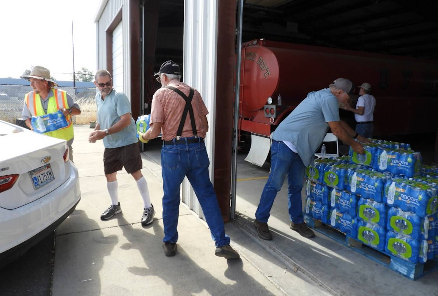 Volunteers at the Orland Fire Department in Glenn County distribute bottled water to people with dry wells on July 28, 2021. August 2021