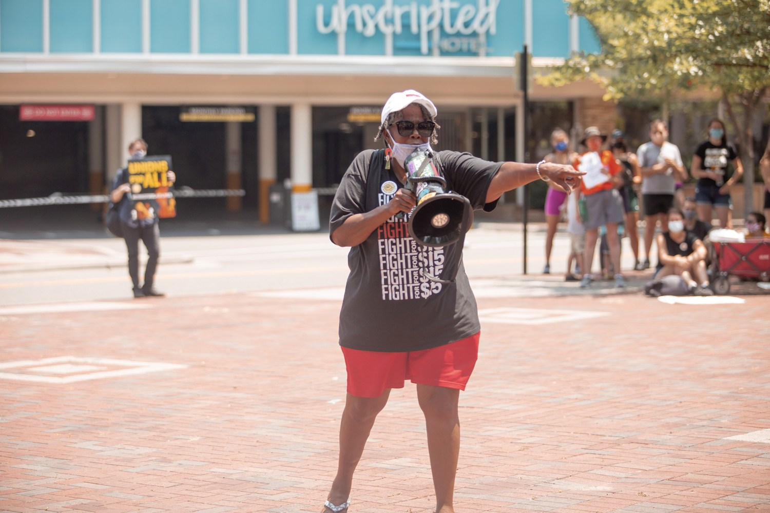 Mama Cookie, July 20, 2021 strike in Durham, NC. She holds a mega phone, wearing a black, Fight for $15 t-shirt and red shorts.