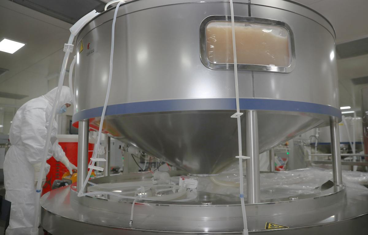 a researcher helps attends a tank of growth media to be used for COVID-19 vaccine production in Nantong, China.
