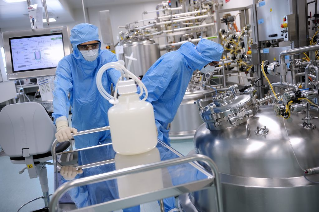 Dengue vaccine production, people wearing hazard suits with gloves, masks, and goggles on in a lab. Culture medium preparation zone. September 2021