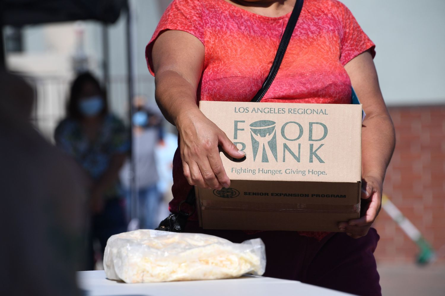A person collects a box of food at a walk-up food distribution bank for people facing economic hardship or food insecurity, in a church parking lot in Los Angeles, California, August 10, 2020 amid the COVID-19 pandemic. September 2021