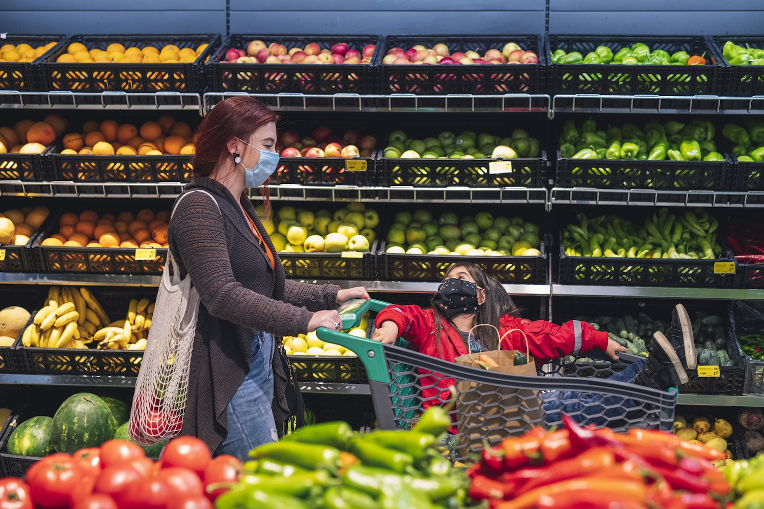 Woman and her little daughter shopping fresh fruits and vegetables in supermarket with protective face mask. October 2021
